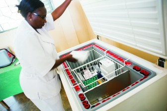 A nurse looks into a refrigerator checking vaccine and supplies stock.
