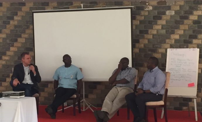 Photo: IntraHealth. Paul Biondich is speaking with Luke Bawo, Olasupo Oyedepo, and Steven Wanyee.