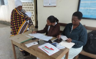 Community health workers consult a range of data sources while attending to a mother and child at an immunization clinic.