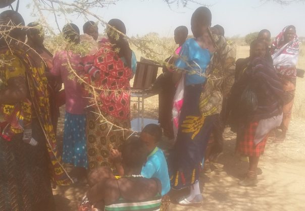 Photo: PATH/Saumu Juma. Mothers with their babies waiting for the outreach clinic to start in Matala village Karatu DC. This clinic sometimes would attend upto 200 babies in one session. With a very remote location, vaccines are brought here by a helicopter from a neighbouring district.