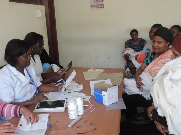 Nurses meet with mothers and infants during an immunization clinic.
